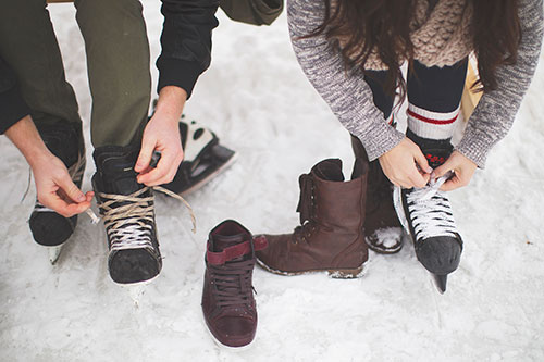 two people tying skates