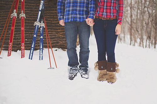 couple holding hands standing by skis